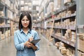 Young Attractive Asian Worker, Owner, Entrepreneur Woman Holding Smart Tablet Looking At Camera With poster