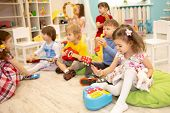 Children Learning Musical Instruments On Lesson In Kindergarten Or Daycare poster