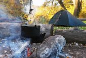 Bonfire And Tourist Bowlers With Cooking Food On The Autumn Forest Background Near The River; Campin poster
