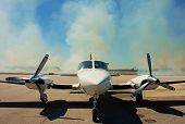 stock photo of cessna  - Twin engine Cessna 421 parked on the ramp with burning grass in the background - JPG