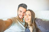 Happy Young Couple Taking A Selfie With Mobile Smart Phone Camera In The Living Room Embracing On So poster