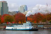 Steaming ferry paddle boat with softer background of trees and the city of Portland