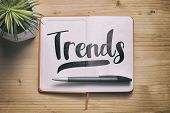 Trends. Trends Concept With A Paper Notebook On The Wooden Desk, Top View. poster