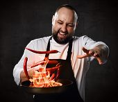 Professional Chef Prepares The Dish With Flame Stirring In A Frying Pan On Kitchen Of The Restaurant poster