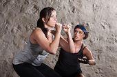 Lady e treinador transpiração durante o exercício de estilo do Boot Camp