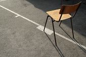wooden schoolchair aligned on white basketball line