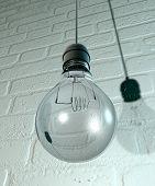 hängende Glühbirne und Verschraubung an der Wand
