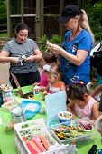 Parents Help Kids With Arts And Crafts Project At Festival