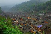 Large village in morning mist, China, mountainous terrain. Zhaoxing Village, Liping County, Guizhou.