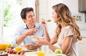 stock photo of breakfast  - Happy Couple Enjoying Breakfast In Kitchen - JPG
