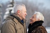 Elderly couple in winter park looking fondly at each other