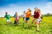 stock photo of boys  - Large group of children running in the dandelion spring field