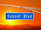 Sunset Blvd overhead street sign with orange dusk sky.