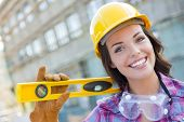 Portrait of Young Attractive Female Construction Worker with Level Wearing Gloves, Hard Hat and Prot