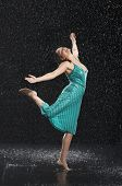 stock photo of dancing rain  - Full length of a young cheerful woman with arms out dancing in rain - JPG