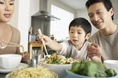 Young parents watching son trying to use chopsticks at dining table
