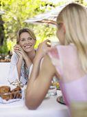 Dos mujeres en mesa de comedor al aire libre y hablando