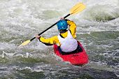 picture of kayak  - an active male kayaker rolling and surfing in rough water - JPG