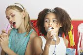 image of slumber party  - Multiethnic young girls using brushes as microphones to sing at a slumber party - JPG
