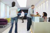 Hombre hablando con la recepcionista de la recepción en la oficina