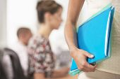 Midsection closeup of a businesswoman carrying folder with blurred colleagues in the background