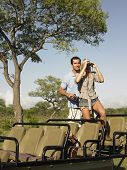 Young couple on safari standing in jeep and looking through binoculars