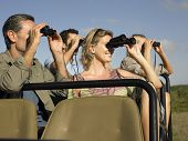 Group of happy tourists sitting in jeep and looking through binoculars
