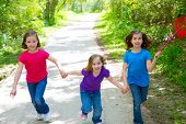 Friends and sister girls running in the forest track smiling happy with butterfly net