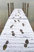 Footprints In Snow On A Dock