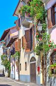 Vertical oriented image of typical italian house with balcony and blinds decorated with flowers in t