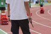 DONETSK, UKRAINE - JULY 11: Official with starting pistol before the 110 meters Hurdles competition