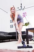 Attractive Cheerful Woman Is In The Room With Vacuum-cleaner.