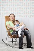 Happy Father Sits With Little Daughter In Rocking Chair At Home.