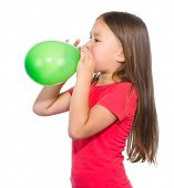 Little girl is inflating green balloon, isolated over white