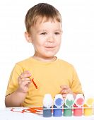 Portrait of a cute little boy playing with paints and making funny grimace, isolated over white