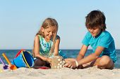 Kids playing on the beach building a sand castle decorating it with seashells