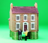 picture of thinkers pose  - A real estate agent and a prospective buyer in front of a house on gold coin stilts - JPG