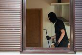 Thief Burglar opening metal door with a crowbar during house breaking