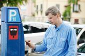 young man paying at parking meter