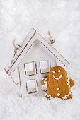 foto of ginger man  - Gingerbread man and wooden house on a festive Christmas snow background - JPG