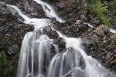 Landscape Detail Of Waterfall Over Rocks In Summer Long Exposure Blurred Motion
