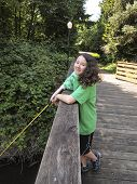 Young Girl Smiles While Fishing Off Bridge