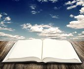 Open book on wooden planks at sky background