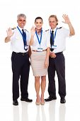 cheerful airline pilots and airhostess waving on white background