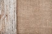 stock photo of rude  - Burlap background bordered by rude old wood - JPG