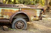 pic of logging truck  - Rusty truck flatbed on flat tire stuck in dirt - JPG