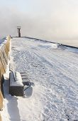 stock photo of boggy  - Blue metal bench on snowy mole and small beacon or lighthouse at the end of the pier - JPG