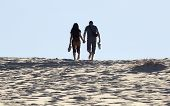 Young Couple Walks On Sand Dune. Fingal Bay. Port Stephens. Australia.