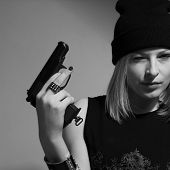 foto of cap gun  - Young girl in a dark cap with a raised gun. Blonde with a gun. monochrome image