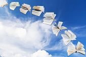 stock photo of blue-bell  - arch of flying books with blue sky and white cloud background - JPG